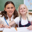 Smiling pupils working together on an assignment — Stock Photo #11209349