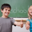 Happy pupils posing with the thumb up — Stock Photo