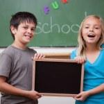 Happy pupils holding a school slate — Stock Photo