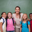 Schoolteacher posing with her pupils — Stock Photo #11209521
