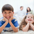 Kids lying on the carpet with parents sitting behind them — Stock Photo