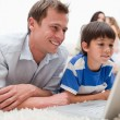Son and father using laptop on the carpet - Stock Photo