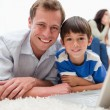Smiling son and dad using laptop on the carpet - Stock Photo