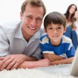 Boy with his father using laptop on the carpet - Stock Photo