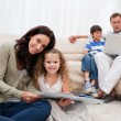 Family spending leisure time in the living room - Stock Photo