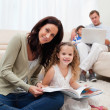 Stock Photo: Mother and daughter reading book together