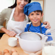 Son and mother preparing cake - Stock Photo