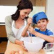 Stock Photo: Mother and son having fun preparing a cake