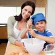 Stock Photo: Mother and son having fun preparing dough