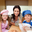 Mother and her children preparing dough — Stock Photo