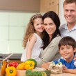 Smiling family standing in the kitchen — Stock Photo #11209608