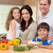 Young family standing in the kitchen - Stock Photo