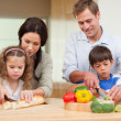 Stock Photo: Family slicing ingredients
