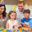 Girl about to blow out the candles on her birthday cake - Stock Photo