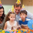 Boy helping his little sister to blow out the candles on her bir — Stock Photo