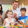 Parents applauding her daughter who just blew out the candles on — ストック写真