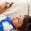Boy playing with his cellphone while lying on the carpet — Stock Photo #11209679