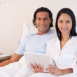 Couple sitting on the bed with their tablet pc — Stock Photo #11209726