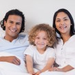 Happy family sitting on the bed together — Stock Photo