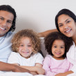 Smiling family sitting on the bed together — Stock Photo