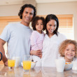 Happy family having breakfast in the kitchen together - Stock Photo