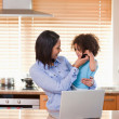 Mother and daughter using laptop and cellphone in the kitchen to — Stock Photo #11209833