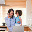 Mother and daughter using cellphone and laptop in the kitchen to — Stock Photo #11209836
