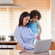 Mother and daughter using laptop in the kitchen together — Stock Photo