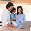 Family using laptop in the kitchen together — Stock Photo