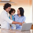 Family using notebook in the kitchen together — Stock Photo