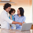 Family using notebook in the kitchen together — Stock Photo #11209844
