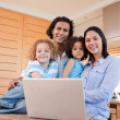 Happy family with laptop standing in the kitchen together — Stock Photo