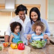 Family preparing salad together in the kitchen — Stock Photo
