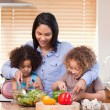Mother and daughters preparing salad in the kitchen together — Stock Photo #11209873