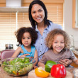 Mother and her daughters preparing salad in the kitchen together — Stock Photo #11209874