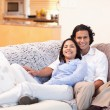 Cheerful couple on the couch together - Stock Photo