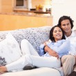 Happy couple on the couch together - Stock Photo