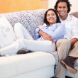 Happy couple relaxing on the couch together - Stock Photo