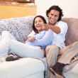 Cheerful couple watching television together - Stock Photo