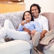 Happy couple watching television together - Stock Photo