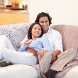 Couple watching television together - Stock Photo