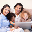 Stock Photo: Family using laptop on the sofa together