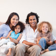 Cheerful family sitting on the sofa together — Stock Photo