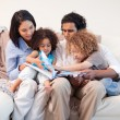 Stock Photo: Family on soflooking at photo album together