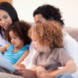 Happy family on the sofa looking at photo album together — Stock Photo