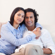 Couple on the couch embracing — Stock Photo
