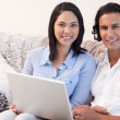 Couple with laptop on the sofa - Stock Photo