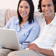Couple with notebook on the couch - Stock Photo