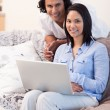 Couple surfing the internet on the couch - Stock Photo