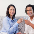 Couple having sparkling wine on the sofa — Stock Photo